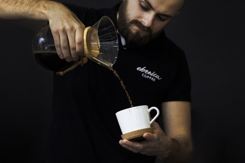 barista pours coffee into white cup