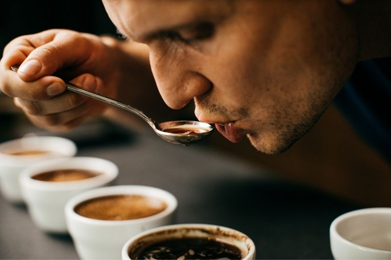 Marek tasting coffee during a cupping